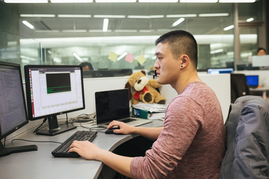 Graduate student exploring computer models on a screen in the lab